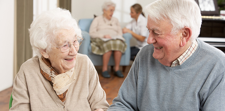 elderly couple smiling fondly at each other with a piano in the background