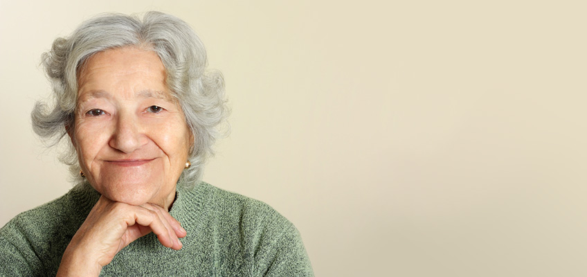 older woman smiling with her hand on her chin