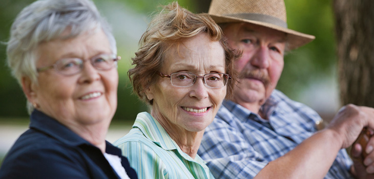 three elderly people smiling sitting on a bench with a tree in the background