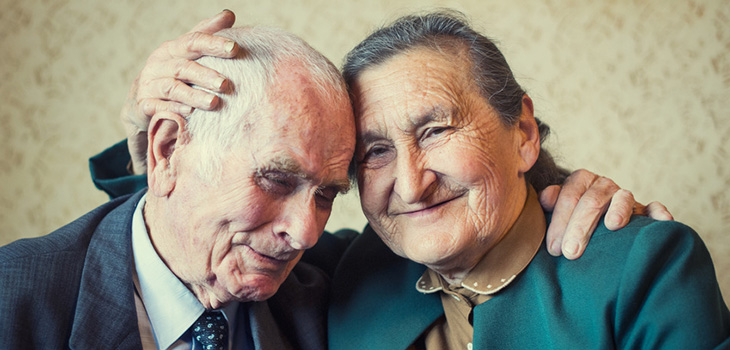 sweet elderly couple with their arms around each other
