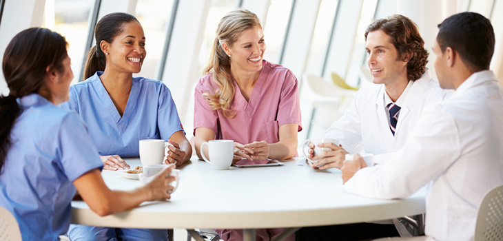 nurses and doctors sitting at a round table having coffee and talking