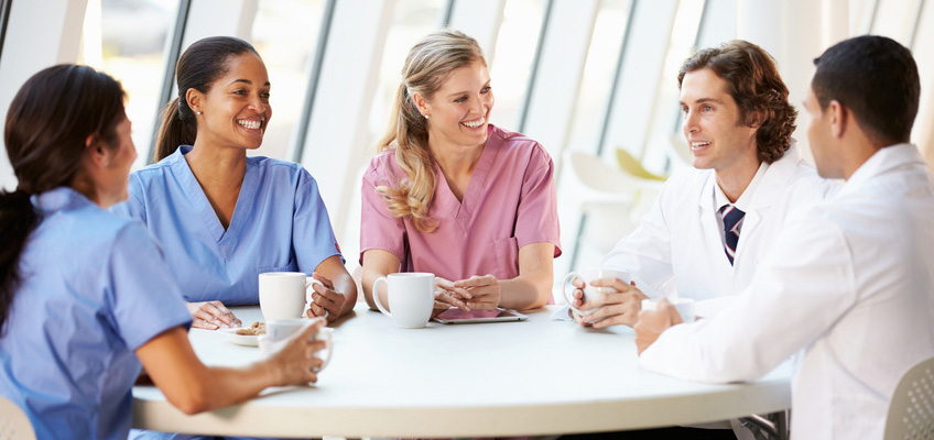 doctors and nurses sitting at a table smiling with coffee