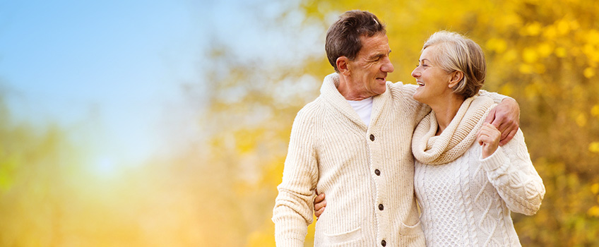 couple wearing wool sweaters taking a walk during fall