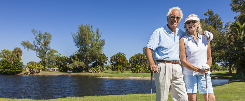 Elderly couple standing by a lake with trees adn grass behind them and golf clubs in hand