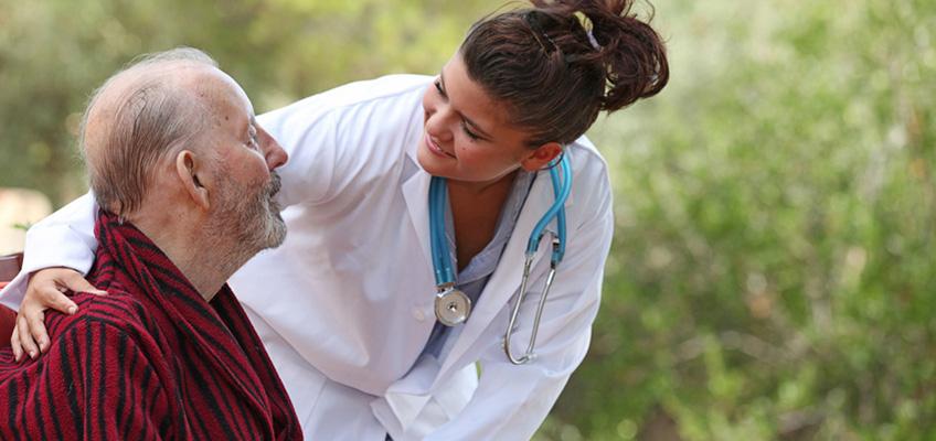 doctor leaning down speaking to elderly resident in wheelchair